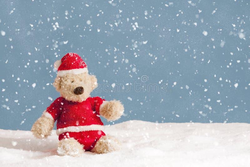 Chute de neige sur l'ours de nounours dans des vêtements de Noël photos libres de droits