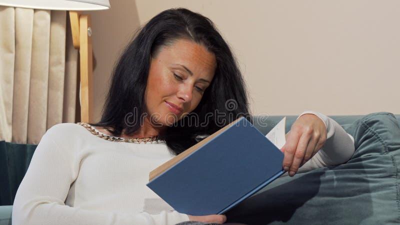 Chute mûre fatiguée de femme endormie tout en lisant à la maison après jour ouvrable images stock
