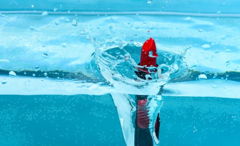 Chute rouge de rouge à lèvres de résistant à l'eau dans le pur, l'eau transparente, fond bleu Concept de cosmétique de résistance photos libres de droits