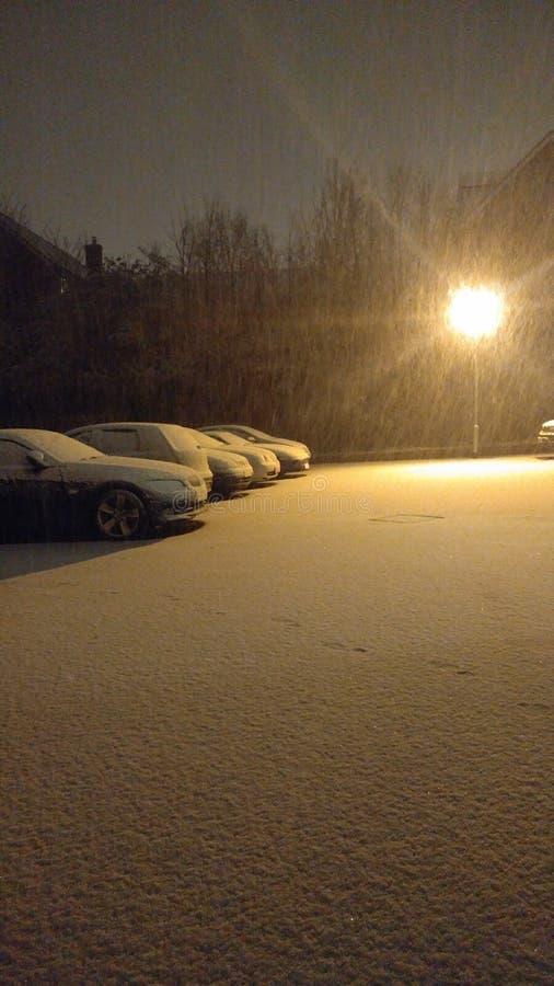 Chutes de neige d'hiver allumées par lumière artificielle images libres de droits
