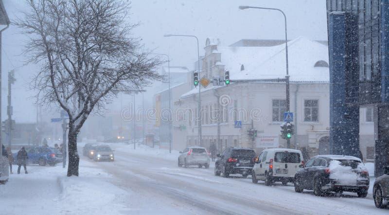 Chutes de neige lourdes dans la ville Les voitures croisant l'intersection, quelques piétons et la neige ont couvert l'arbre photo libre de droits