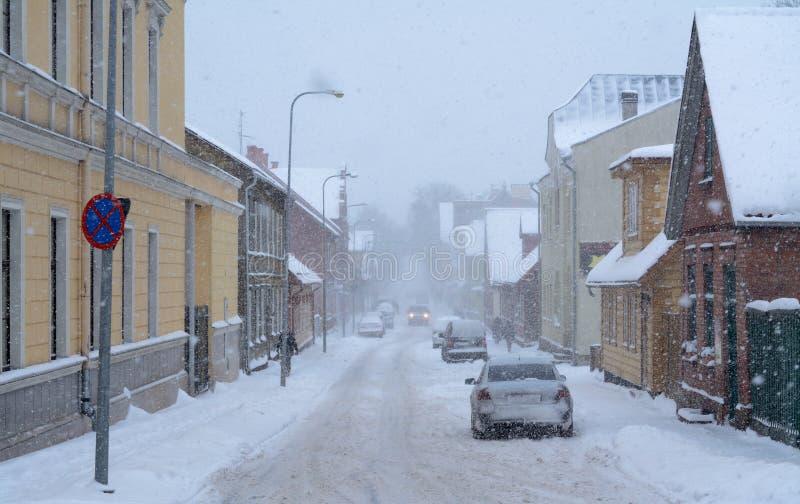 Chutes de neige lourdes dans la ville, quelques piétons et des voitures sur la rue photos stock