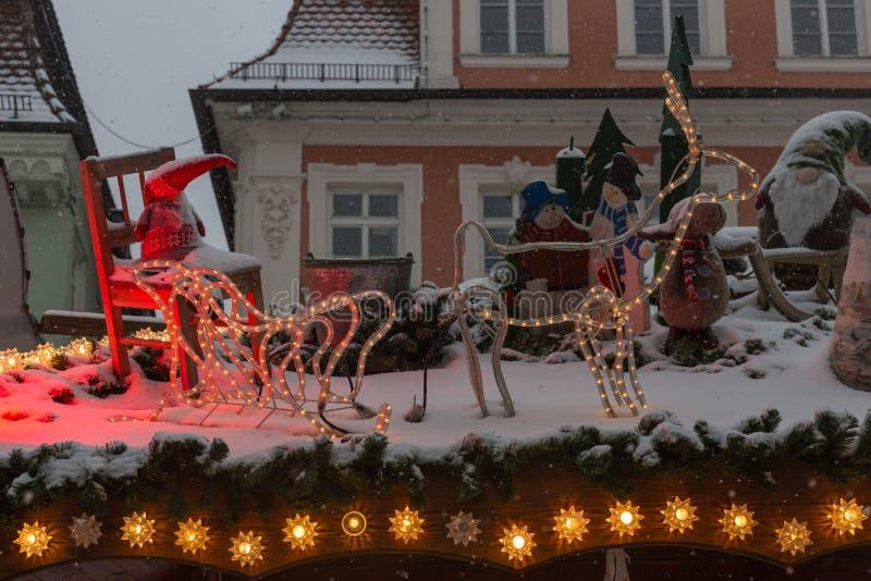 chutes de neige sur le marché de Noël avec les lampes et la décoration de lumières dedans images stock