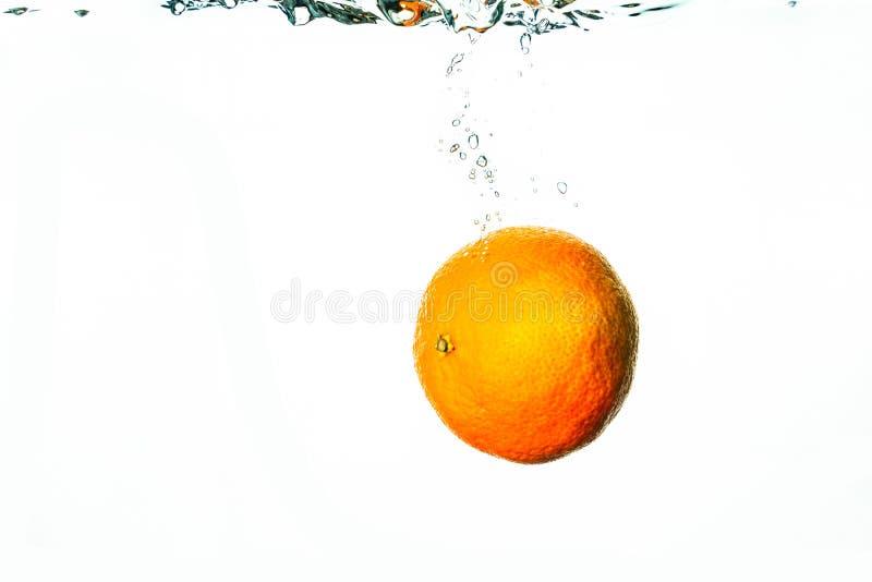 Chutes oranges fraîches dans l'eau avec des bulles image libre de droits