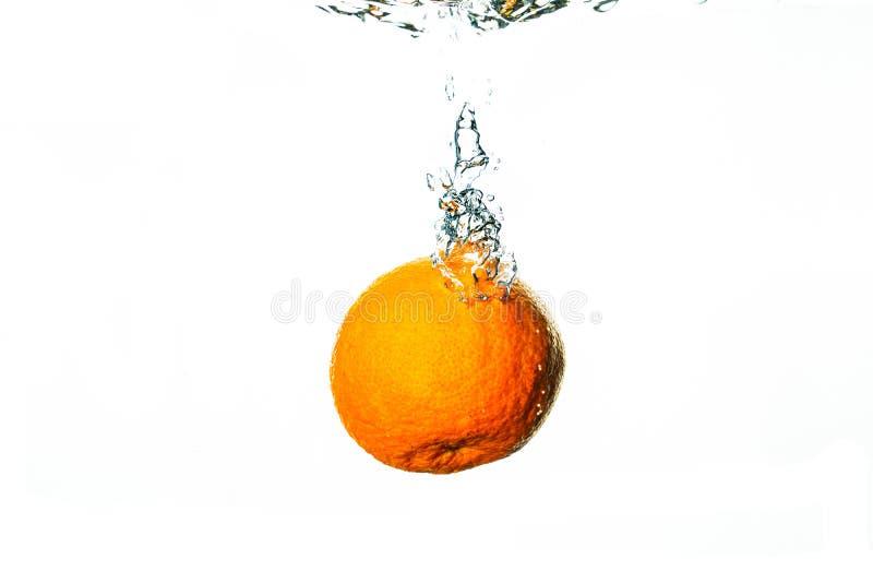 Chutes oranges fraîches dans l'eau avec le fond blanc photos libres de droits