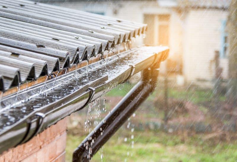 A chuva derrama no telhado As rupturas do sol completamente foto de stock