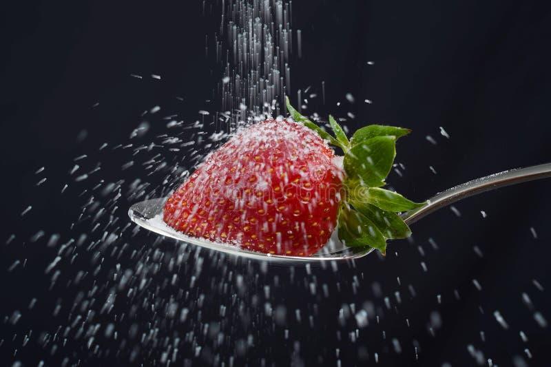 A chuva do açúcar polvilha sobre a morango deliciosa na colher que derrama para fora em toda parte fotografia de stock