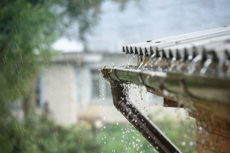 A chuva flui para baixo de um telhado para baixo foto de stock