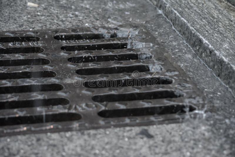 Chuva pesada que deixa de funcionar no pavimento de estrada e na câmara de visita fotografia de stock royalty free