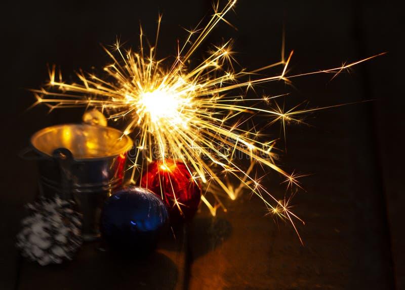 Chuveirinho de queimadura atrás de uma bola de vidro em um fundo de madeira preto imagens de stock