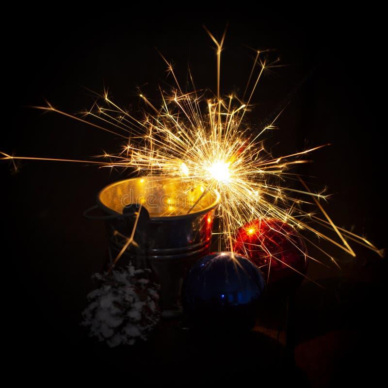 Chuveirinho de queimadura atrás de uma bola de vidro em um fundo de madeira preto foto de stock