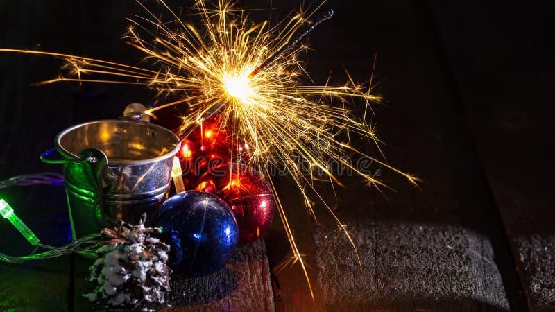 Chuveirinho de queimadura atrás de uma bola de vidro em um fundo de madeira preto foto de stock royalty free