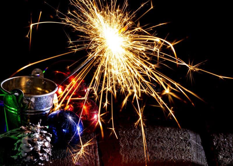Chuveirinho de queimadura atrás de uma bola de vidro em um fundo de madeira preto fotos de stock