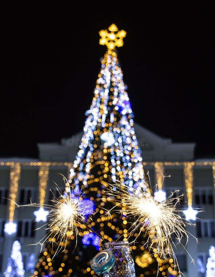 Chuveirinho do fundo do sumário do feriado do bokeh do borrão da noite da luz da árvore de Natal no primeiro plano foto de stock