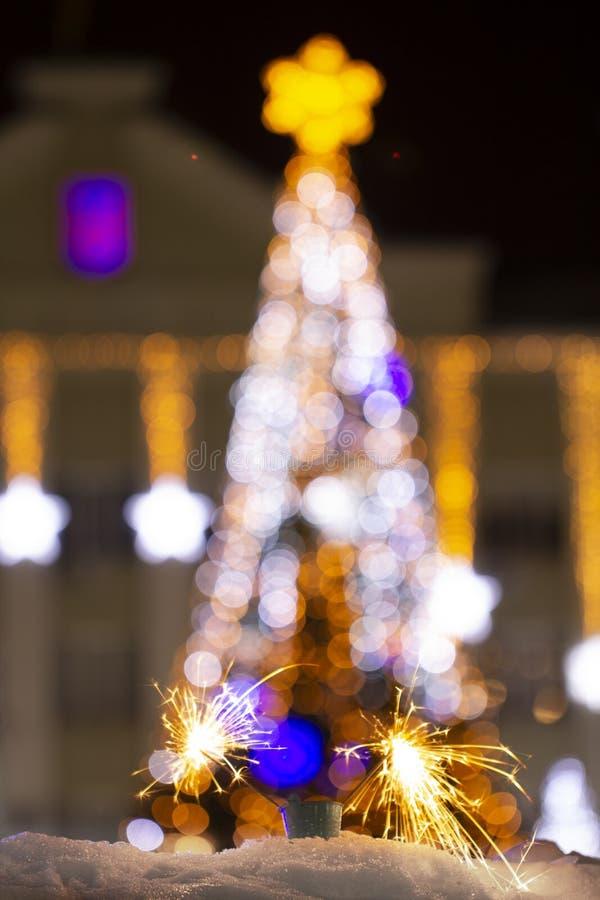 Chuveirinho do fundo do sumário do feriado do bokeh do borrão da noite da luz da árvore de Natal no primeiro plano imagens de stock