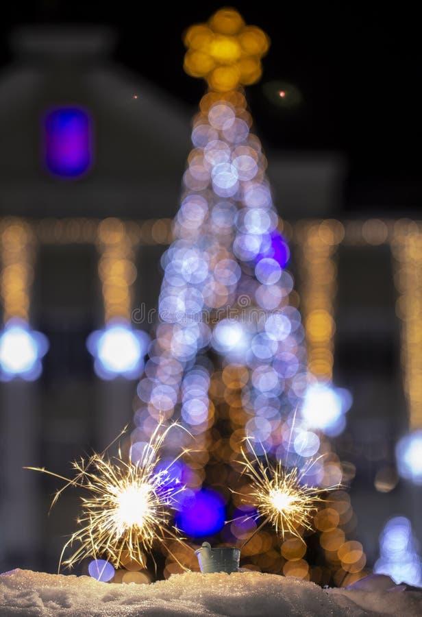 Chuveirinho do fundo do sumário do feriado do bokeh do borrão da noite da luz da árvore de Natal no primeiro plano imagens de stock royalty free