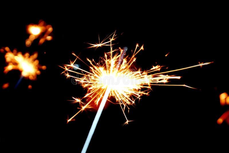 Chuveirinhos festivos em um fundo preto Os povos iluminaram os chuveirinhos sob o pulso de disparo chiming pelo ano novo fotografia de stock