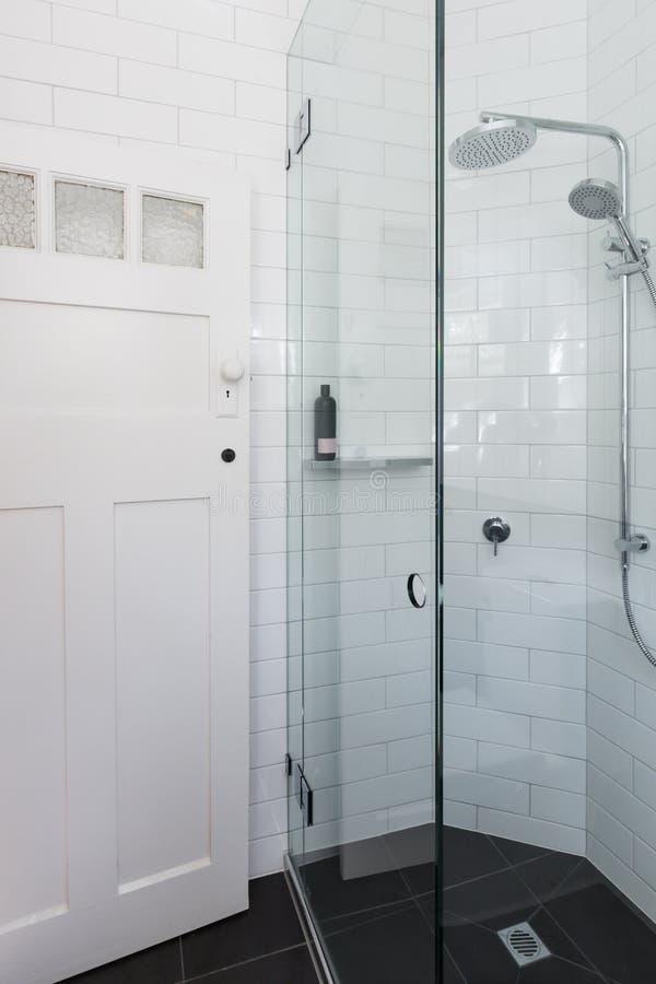 Chuveiro branco moderno na renovação do banheiro com o si do teste padrão do tijolo foto de stock