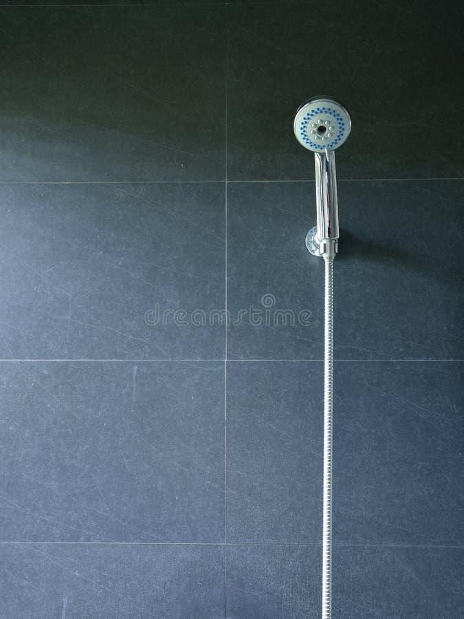 Chuveiro do banho na parede preta da telha fotografia de stock royalty free