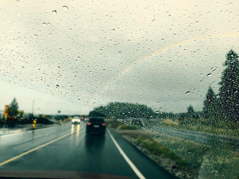 Chuvisque no para-brisa ao conduzir na chuva Estrada e arco-íris molhados no céu imagem de stock