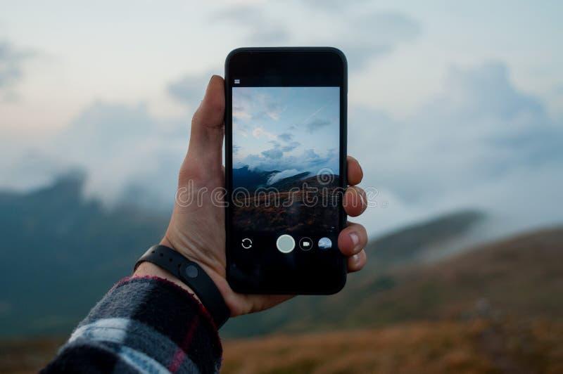 Chwytać pięknego góra krajobraz z chmurą na smartphone mężczyzna trzyma jego smartphone chwyta góry zdjęcia royalty free