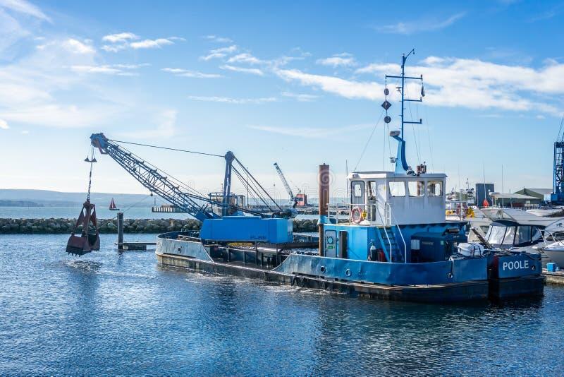 Chwyta bagieru C H róg przy pracą bagruje Poole schronienia marina w Dorset, UK zdjęcie royalty free