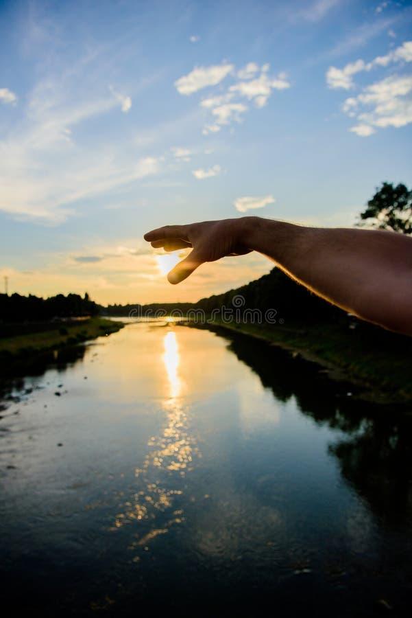 Chwyta ostatni sunbeam Męska ręka wskazuje przy słońcem w niebieskim niebie przy wieczór czasem podziwia krajobraz Rzeczny słońca obraz royalty free