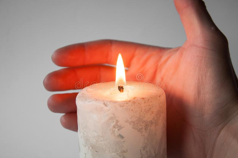 Chwyty wręczają blisko płonącej białej świeczki fotografia stock