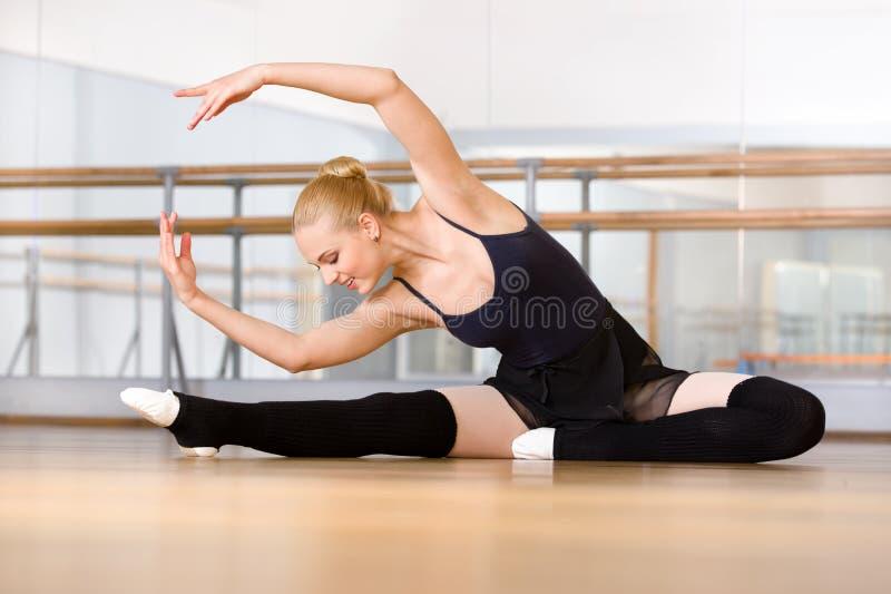 Chylenie baleriny rozciągliwość herself na podłoga obraz royalty free
