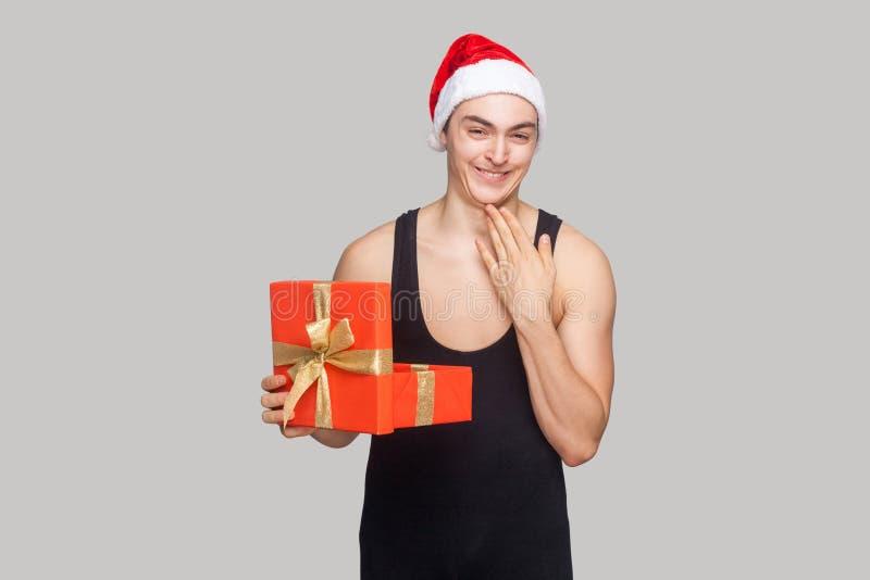 Chytry mężczyzna dotyka jego podbródek w czerwonym kapeluszowym mienie prezenta pudełku i obrazy royalty free