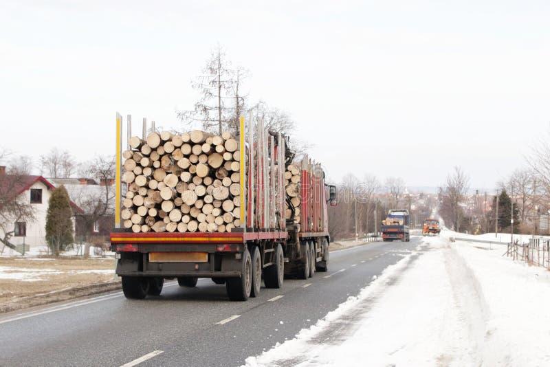 Ciężarówka z przyczepą niesie bele wzdłuż śnieżystej asfaltowej drogi Usunięcie drewno dla przetwarzać Przemysłowa zimy wyróbka obraz stock