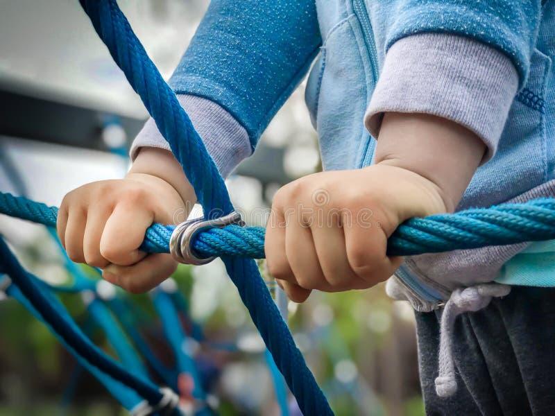 Ciérrese de las manos del muchacho detiene la cuerda en la red que sube de la cuerda imagen de archivo