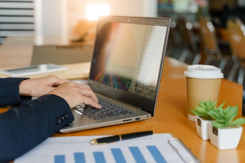 Ciérrese de las manos de la persona del negocio consume trabajos de teclado del ordenador portátil en la oficina con la taza de c foto de archivo