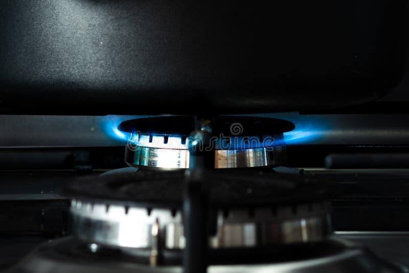 Ciérrese de una cacerola negra se incorporó encima de una llama abierta de un avellanador del gas que calienta encima del conteni imagenes de archivo
