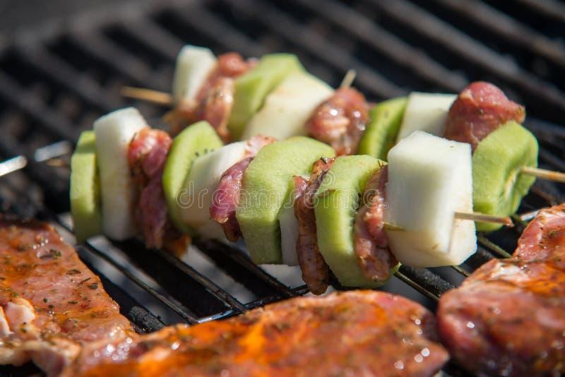 Ciérrese en la carne cruda con las frutas en la parrilla imagen de archivo