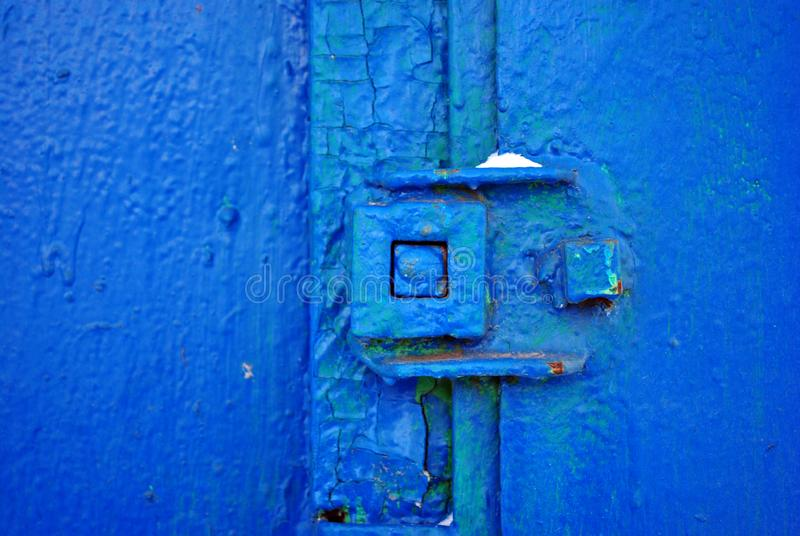 Ciérrese en la puerta vieja con una pintura azul brillante lamentable, fondo del hierro del grunge fotografía de archivo