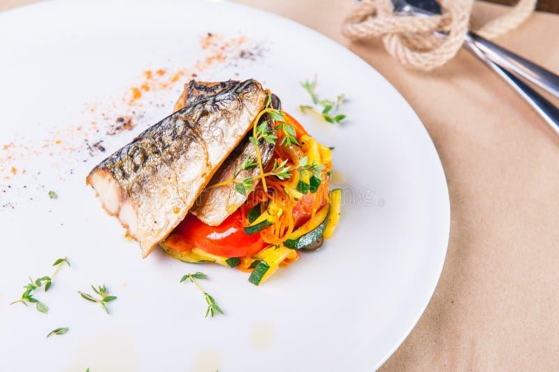 Ciérrese encima de asar a la parrilla el filete de pescados con la almohada vegetal servida en la placa blanca Porción del restau fotografía de archivo
