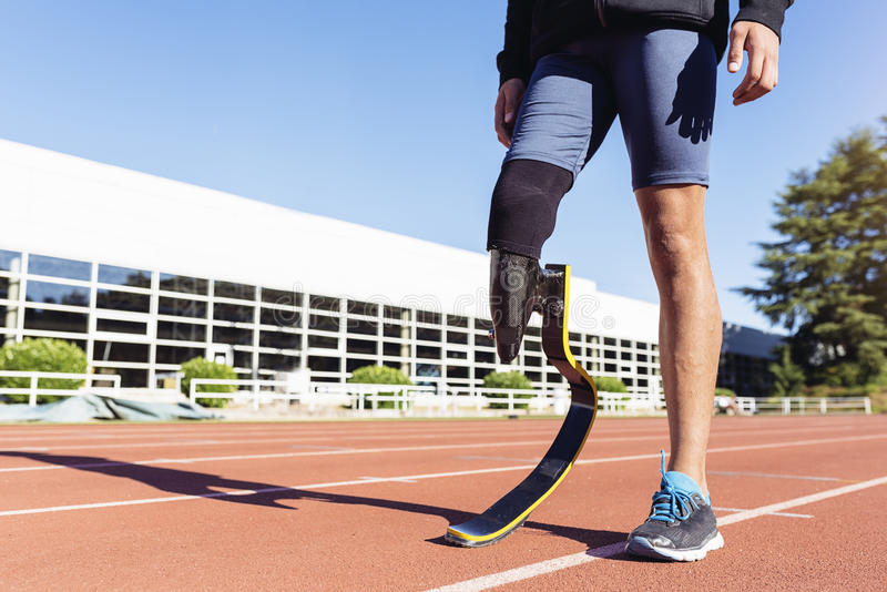 Ciérrese encima de atleta discapacitado del hombre con la prótesis de la pierna imagen de archivo libre de regalías
