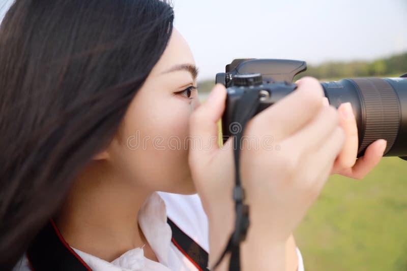 Ciérrese encima de cámara china del control del fotógrafo de la mujer de Aisan cerca de su trabajo de la cara en naturaleza contr imagenes de archivo