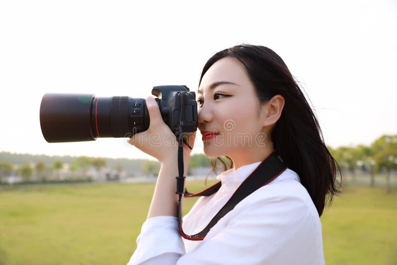 Ciérrese encima de cámara china del control del fotógrafo de la mujer de Aisan cerca de su trabajo de la cara en naturaleza contr fotos de archivo