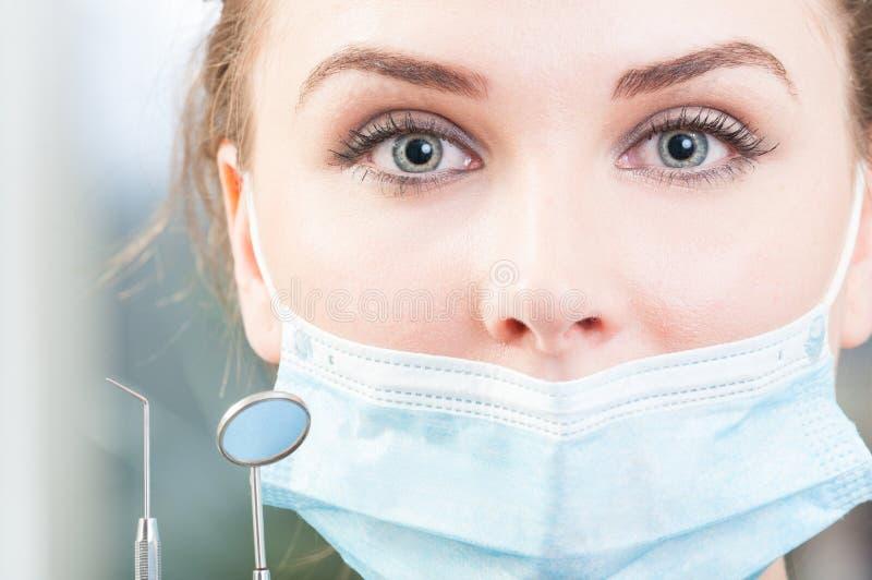 Ciérrese encima de cara atractiva del dentista con las herramientas y enmascare fotografía de archivo libre de regalías