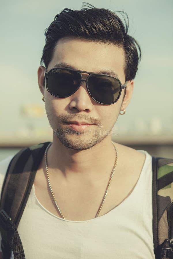 Ciérrese encima de cara de la colocación de los vidrios de sol de un hombre que lleva asiático más joven fotografía de archivo libre de regalías