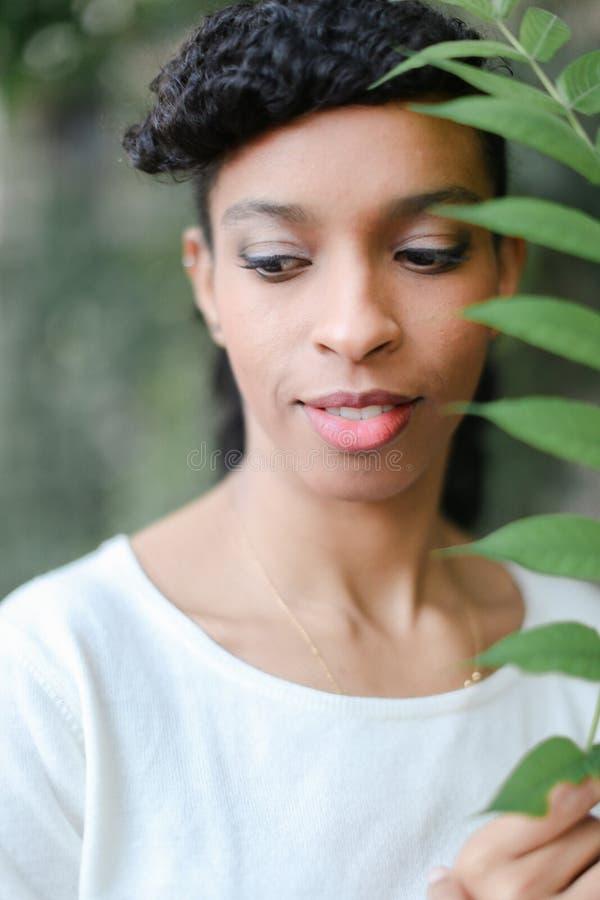 Ciérrese encima de cara de la muchacha bonita negra que guarda la hoja verde, teniendo blusa blanca de las explosiones y el lleva fotografía de archivo libre de regalías