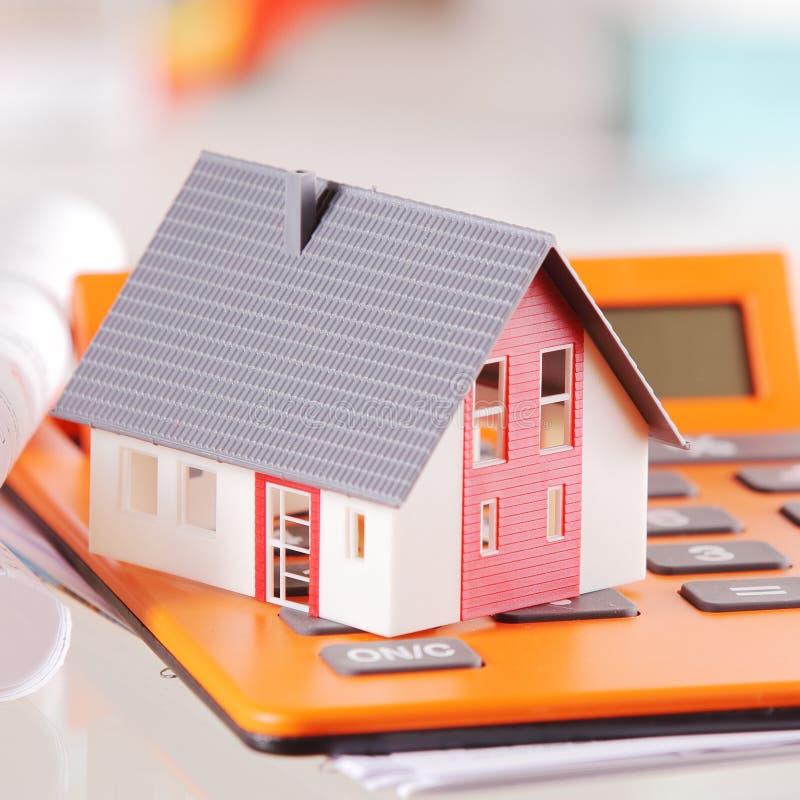 Ciérrese encima de casa miniatura encima de una calculadora foto de archivo