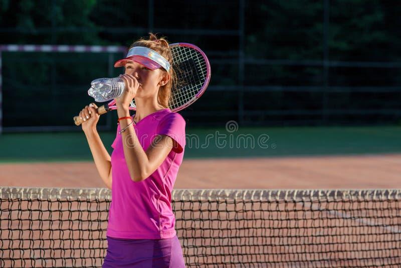 Ciérrese encima de chica joven linda en agua potable del casquillo deportivo de la botella plástica después del entrenamiento dur foto de archivo