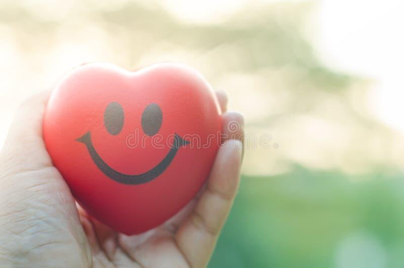 Ciérrese encima de corazón rojo de la sonrisa de la tenencia de la mano con el fondo ligero fotos de archivo libres de regalías