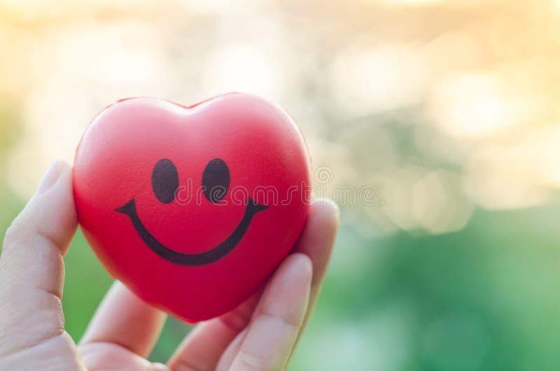 Ciérrese encima de corazón rojo de la sonrisa de la tenencia de la mano con el fondo ligero fotos de archivo