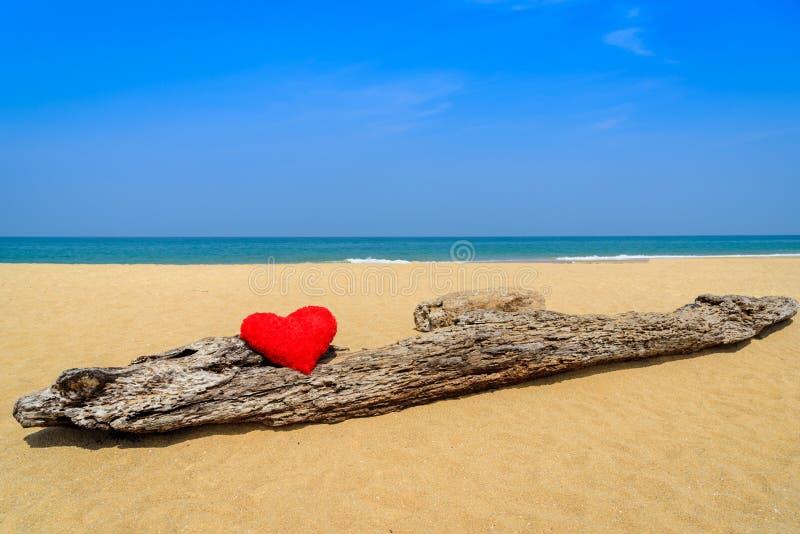 Ciérrese encima de corazones rojos en la arena de la playa del océano foto de archivo