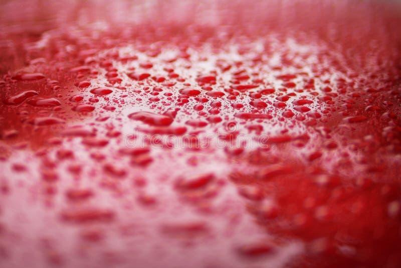 Ci?rrese encima de descensos del agua en el serface rojo del coche para el fondo fotografía de archivo libre de regalías