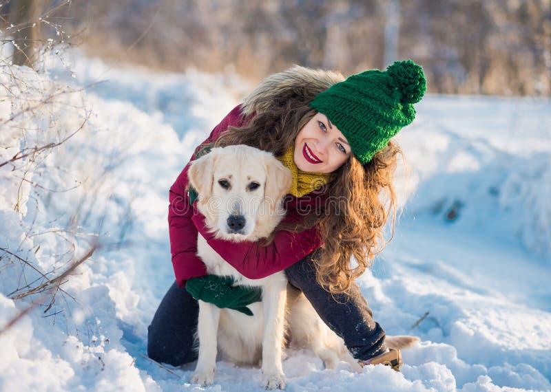 Ciérrese encima de dueño feliz de la mujer y del perro blanco del golden retriever en día de invierno fotografía de archivo